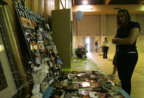 Paulette Kowalski of Salem looks at photo collages of Julie Gauthier, a Salem teen who was killed in a car accident in March. On Friday evening a benefit concert was held at Salem State College in honor of Julie to raise money for the new scholarship fund established in her name. PHoto by deborah parker/may 7, 2010
