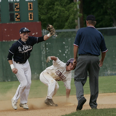 St. John's Derek DuBois signals to the umpire that he has the ball for the out against Lowell's Kyle Gath during yesterday's Division 1 North Sectional Semi Finals game held at Alumni Field in Lowell. Photo by Deborah Parker/June 4, 2009