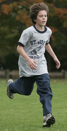 Ryan Dzengelewski, a sixth grade student at St. John's of Peabody, runs to the finish line during their cross country meet against St. Mary's of Melrose held at Emerson Park in Peabody Thursday afternoon. Photo by deborah parker/october 14, 2010
