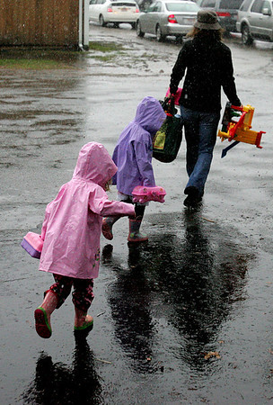 Karen Duval of Topsfield and her two twins, Emma and Nora, 3, run through the rain to their car after shopping at the Toy Fair held at the Topsfield Fair Grounds Saturday morning. Photo by Deborah Parker/November 14, 2009