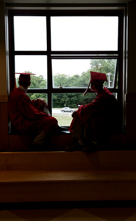 David Burbank, left, and Justin Buzzotta, both of Boxford, look for friends entering the high school before the start of graduation at Masconomet Regional High School Friday evening. Photo by Deborah Parker/ June 5, 2009