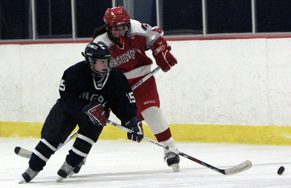 Wenham: Pingree's Meaghan Souza and Masconomet's (*didn't have numbers*) fight for control of the puck during the Pingree Holiday Tournament held at Johnson Rink Saturday. <br /> Photo by Deborah Parker/Salem News Saturday, December 13, 2008