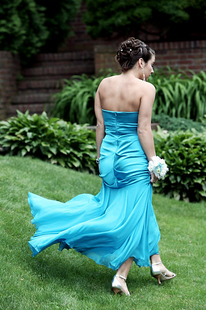 The dress of Tayna Tarnowski, a senior at Beverly High School, flows in the air as she makes her way from one photo opt to the other while taking pictures at Lynch Park before the start of prom Thursday evening. Photo by Deborah Parker/June 11, 2009