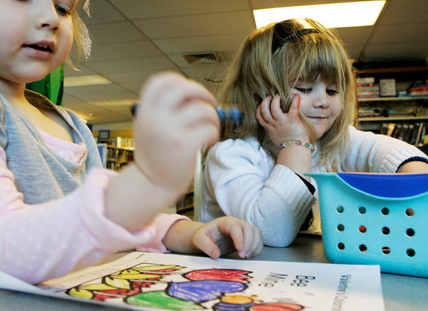 Peabody: Carly Pence, 4, left and Trinity Brown, 4, both of Peabody became instant friends over their love of coloring while spending the morning with their moms at the Peabody Institute Library Thursday. Photo by Deborah Parker/Salem News Thursday, January 29, 2009.