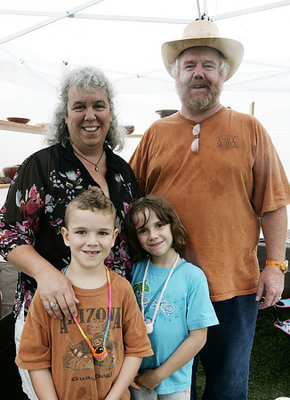 The Souter family from Ipswich, Michael, 6, Samantha, 8, and their parents, Michelle and Michael, pose for a picture at their stand during the Olde Ipswich Days Arts and Crafts Fair Friday afternoon. Photo by Deborah Parker/July 24, 2009