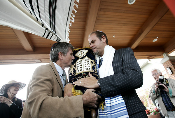 After leading a processional through Brooksby Village, Paul Cohen of Shelborn Falls passes a sacred torah donated by Congregation Ahabat Sholom in Lynn, to Colman Reaboi, the Spiritual Leader and Pastoral Associate of the Jewish community at Brooksby Village. The torah was donated in memory of Cohen's father, Victor Cohen, who lived at Brooksby Village.  Photo by Deborah Parker/Septmeber 10, 2009