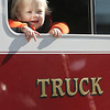 Owen Martineau, 1, of Ipswich, pokes his head out the window of a fire truck while at the Ipswich Fire Station during their open house Saturday morning. Photo by Deborah Parker/October 9, 2010