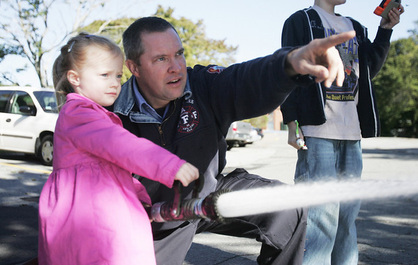 Fire fighter Jeremy Dalton shows Claire Buletza, 3, of Ipswich how to handle the fire hose as part of a demonstration while at the Ipswich Fire Station during their open house Saturday morning. Photo by Deborah Parker/October 9, 2010