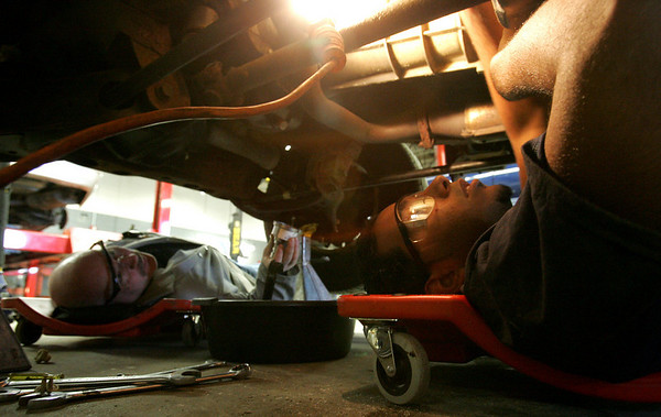 J.C. Perez, a junior at the Peabody High Vocational School located inside Higgins Middle School, along with auto body teacher Ken Gannon, works on a car while at the school's auto shop. Photo by Deborah Parker/November 17, 2009