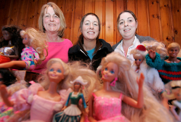 Ipswich: From left, Patty Pallazola of Ipswich and her two daugthers, Megan and Erin sit behind their large Barbie Collection that the girls played with when they were young. Photo by Deborah Parker/Salem News Friday March, 6, 2009.
