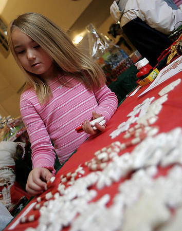Beverly : Breanna Olson, 5, of Salem carefully picks out ornaments to give to her family members while visitng Salem's St. Peter's Episcopal Church Holiday Extravaganza Saturday. The event included, a raffle, along with several tables with crafts and food items to purchase. Photo by Deborah Parker/Salem News Saturday, November 15, 2008