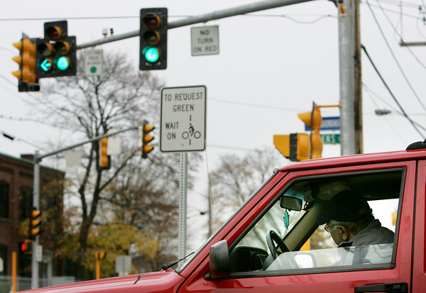 Last spring, the city put in a new traffic light at the intersection of Washington Street and Allen's Lane. It has caused headaches for Sotirios Korisianos and his wife Bessie. When they pull out of their driveway, they can't tell if the light is red or green and they often find that the traffic blocks their access to the driveway from the street. Here Sotirios demonstrates how he has to lean far over to see what color the light is while at the end of his driveway. Photo by Deborah Parker/November 10, 2009