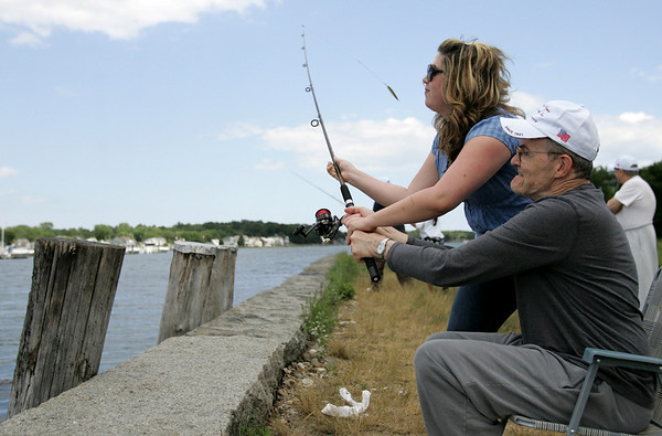 Jessica Dupont, the director of Activities at the New England Homes for the Deaf, helps resident Paul Lindsly cast off his fishing reel into the Danvers river off their Danversport property. Recently, a fishing club was started for the residents, that meets every Friday in coordination with the tide. Photo by Deborah Parker/July 30, 2010