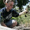 Heather Trethaway, 12, of Beverly works on cleaning up the weeds in the front yard of her home on Mill Street as part of the Gloucester Crossing cleanup day on Saturday. Photo by Deborah Parker/May 30, 2009
