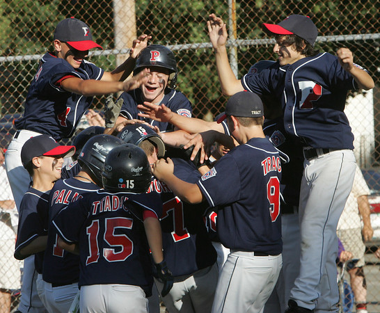 Peabody West's Zack Crawford is congratulated at home plate by his teammates after the first home run of the game during the Little League Sectional Championship held at Weafer Park in Worburn, Monday evening. Photo by Deborah Parker/July 25, 2010