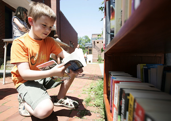 James Hurley, 8, of Burlington browses through a selection of books in front of the Beverly Farm Library  as part of their book sale Friday afternoon. The library along with other Farms businesses are participating a sidewalk bazaar this weekend with outdoor stands, arts and crafts, and even a barbecue. Photo by Deborah Parker/July 10, 2009