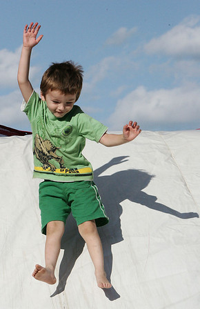 Collin Burns, 3, of Salem leaps off a bouncy house slide during Kid's Night at the Salem Commons, part of Salem Heritage Days. Photo by Deborah Parker/August 7, 2009