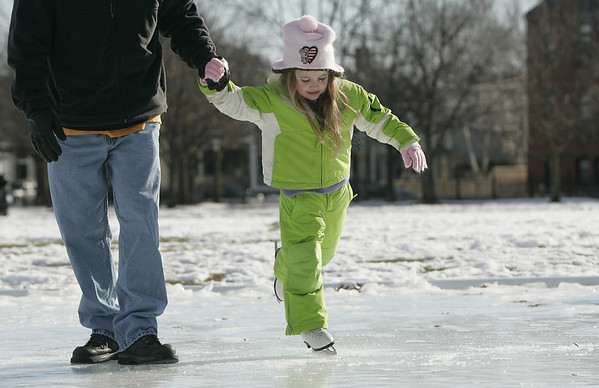 Salem: Olivia Cook, 3, of Marblehead tries out her new skates with her dad, Scott Lyons while at the Salem Commons Friday afternoon. Photo by Deborah Parker/Salem News Friday, December 26, 2008