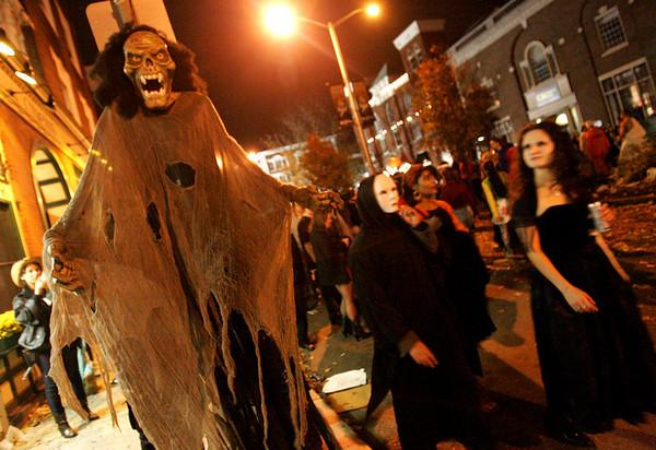 Halloween revelers walk past a scray decoration on Washington Street Halloween evening. Photo by Deborah Parker/October 31, 2009