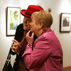 Nancy Haynes of Lynnfield, in pink, and Lisa Ward of Amesbury examine the work of painter Terry Del Percio-Piemonte during the opening of her and her husband, David Piemonte's show at the Centennial Gallery at The Musculoskeletal Center. Photo by Deborah Parker/November 23, 2009