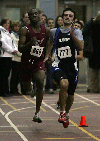 Lynn English's Camy Ducasse and Peabody's Jon Aquaviva compete in the 300 meter during last night's meet against Marblehead and Lynn English held at Marblehead High School. Photo by Deborah Parker/January 11, 2009