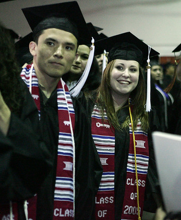Salem Patrick McDermott of Danvers and Kathryn Stallard of Marblehead try to get the attention of a professor during the processional of the Salem Sate College graduation Saturday. Photo by Deborah Parker/May 16 ,2009