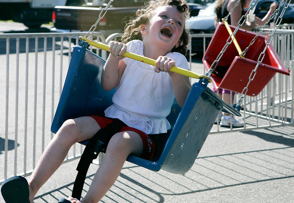 Pia Cormier, 3, of Peabody giggles as she spins on a swing ride during the Danvers Family Festival before the annual fireworks Sunday evening. The festival included a dj, food, rides, games and bouncy houses. Photo by Deborah Parker/July 5, 2009.