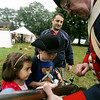 Amelia Silvestro, 6, and her brother, Sam, 7, of Peabody get a first hand look at how gun was loaded during Revolutionary War times by reenactor Paul Kenney of Weymouth while visiting the Rebecca Nurse Homestead with their dad, Steve. The Danvers Alarm List Company hosted The Battle of Crane Brook, a celebration of 18th century colonial life this weekend at homestead. Photo by Deborah Parker/October 4, 2009