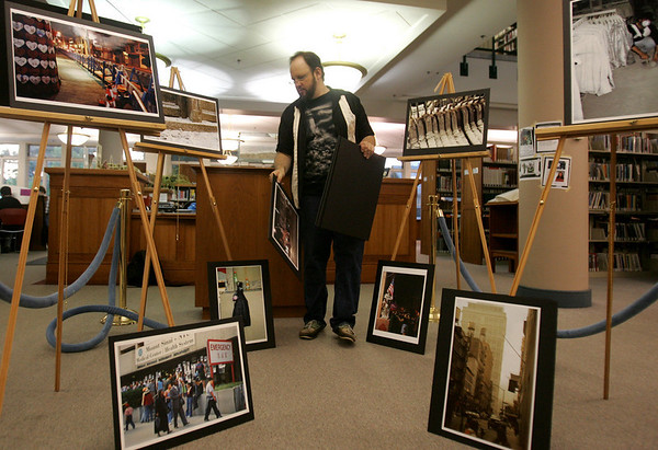 "Artist Dave Gordon sets up his exhibition, ""And Then There Was Quiet: New York After the Attack,"" at the Beverly Public Library Tuesday evening. The show features photographs of the aftermath of the Sept. 11, 2001, attack on New York City. It will run at the libary from Sept. 1-30. Photo by Deborah Parker/August 31, 2010"
