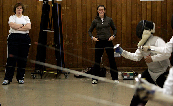 Peabdoy: Jane Carter and Molly Sullivan watch a fencing drill during the Tanner City Fencing Club practice held at Higgins Middle School Wednesday evening. Coach Molly Sullivan Sliney is a former Olympian and partner coach, Jane Carter is a Pan American games gold medalist. Photo by Deborah Parker/Salem News Wednesday, December 17, 2008.