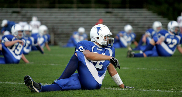 Danvers' Corey Walker stretches with his teammates before the start of the Falcon's game against Rever under the lights at Deering Stadium Friday evening. Photo by Deborah Parker/September 25, 2009