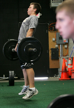 "Jake Bugler, a member of the Bishop Fenwick football team, works on a weight lifting drill as part of ""gridiron training"" with athletic trainer Pat Downey.  Downey has started his own business working with many local high school players and teams. He is focusing on hardcore performance with individuals and specific teams. He previously served as a pro football strength and conditioning coach. Photo by Deborah Parker/September 30, 2009"