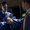 Bobby Owens, left, shakes hands with 2009 class secretary Juan Vega as the students lined up before the start of the graduation ceremony Saturday afternoon. Photo by Deborah Parker/June 6, 2009