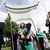 Executive Director of Brooksby Village, Tim Wingardner, left, along with Director of Resident Life, Helen Hangan, lead a processional through the community as Esta Lichtenstein of Framingham carries a sacred torah donated to the community by Congregation Ahabat Sholom in Lynn. Photo by Deborah Parker/Septmeber 10, 2009