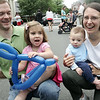 Mitch Surowiec of Beverly and his wife, Lisa, laugh as their two children, Evelyn, 3, and Emmett, six months, avoid looking at the camera while having their photograph taken at the Beverly Arts Festival on Cabot Street Saturday. Along with art vendors there were games for kids, a dj, and food. Photo by Deborah Parker/June 20, 2009.