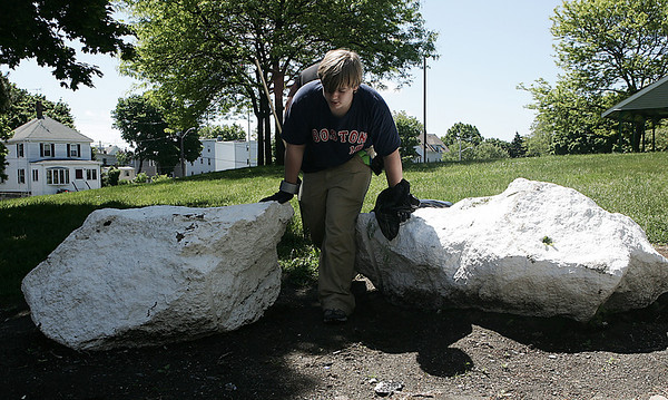 Tom Wells, 16, of Beverly searches around the the park at Gloucester Crossing for any trash that they may have missed while participating in the neighborhood's cleanup day on Saturday. Photo by Deborah Parker/May 30, 2009