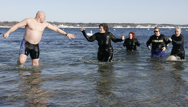 Salem: Ali Karaa of Swampscott gives Jaimie Hoover of Malden a high five as Elizabeth Black of Beverly, Maureen Olson of Malden and Becky Christie of Salem quickly make their way out of the water during yesterday's Polar Swim at Juniper Point Beach. This is the ninth year that a group of people have gathered to jump into the frigid water. Photo by Deborah Parker/Salem News Thursday, January 01, 2009