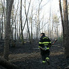 Danvers Jim Ciman walks through a wooded area behind Danvers High School where a brush fire burned Wednesday afternoon. Photo by Deborah Parker/April 14 ,2010
