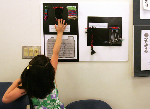"""Corinne Ly of Salem reaches up to touch one of the project part of the """"The Weaving Project"""" on display at Salem State College. First and second graders at Salstonstall praticiapted in the project, funded by a grant from the Salem Education Foundation. An opening reception was held at Salem State College Monday evening. Photo by Deborah Parker/May 3, 2010"""