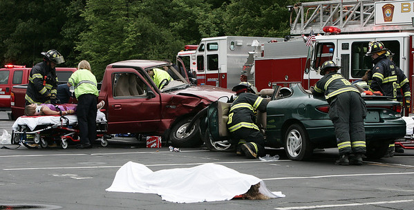 """Members of Beverly High School peer leadership team along with the Police and Fire departments simulate an after party car crash in a parking lot at the school Wednesday. In preperation for prom the mock crash was held to encourage students to realize what could happen if they drink and drive after prom or any event. In the foreground peerd leader, Thyra Rollins lays on the ground while fellow leader, Erin Bushey is pulled from a car during the """"crash"""". Photo by Deborah Parker/June 10, 2009"""