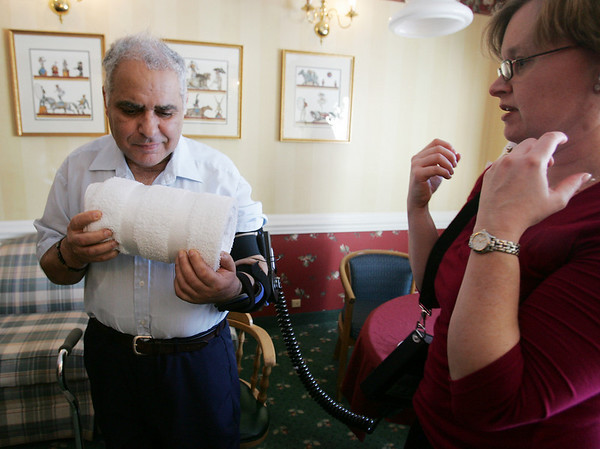 Manuel Machado, a stroke victim from Peabody, deomonstrates, with the help of Rehab Manager for Northeast Home Care, Saron Gonick,  a new robotic brace now available to help stroke victims recover the use of their arms. Northeast Senior Health, which runs Ledgewood, said they are the first organization in the country to use the MIT-developed technology, called Myomo, which stands for My Own Motion. Photo by Deborah Parker/January 27, 2009