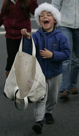 Marblehead: Jack Sears, 5, of Marblehead is all smiles as he passes out candy while marching with the Marblhead Youth Badminton group in the Christmas parade Saturday. Photo by Deborah Parker/Salem News Saturday, December 06, 2008