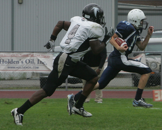 Peabody's Jason Hiou easily outruns Cambridge's Marvin Bonhomme for a touchdown during Friday afternoon's game held at Peabody Veteran's Memorial High School. Photo by Deborah Parker/September 17, 2010