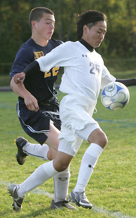 Hamilton-Wenham's Tomoki Sato keeps the ball from Lynnfield's Brenden Colby during yesterday's game in Hamilton. Photo by Deborah Parker/October 8, 2009