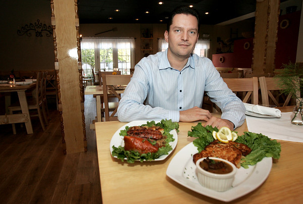 Darek Barcikowski, owner of Cafe Polonia which recently opened in downtown Salem, sits in the restaurants dining room with the Polish platter and a plate of potato pancakes. Photo by deborah parker/october 13, 2010