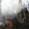 Fire fighter Marc Santorella works to extinguish flames burning in a tree, part of a brush fire in a wooded area behind Danvers High School Wednesday evening. Photo by Deborah Parker/April 14, 2010