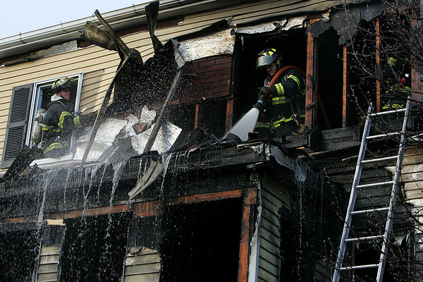 Fire fighters work to extinguish a fire at 30 Harris Street in Peabody yesterday afternoon. Photo by Deborah Parker/January 26, 2009