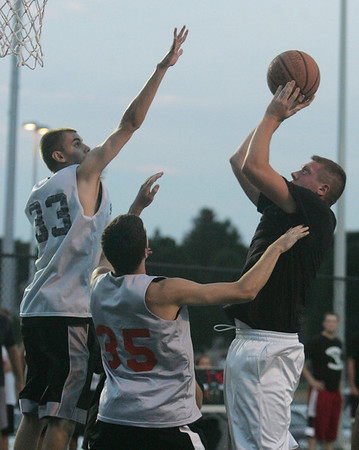 Peabody's Brian DeAngelis is defended in front of the net by Beverly's Chris Keaton and Dan Cacciatore during Monday night's North Shore Summer League basketball game held at Plains Park in Danvers. Photo by Deborah Parker/August 2, 2010