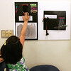 "Corinne Ly of Salem reaches up to touch one of the project part of the ""The Weaving Project"" on display at Salem State College. First and second graders at Salstonstall praticiapted in the project, funded by a grant from the Salem Education Foundation. An opening reception was held at Salem State College Monday evening. Photo by Deborah Parker/May 3, 2010"