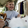 Luke Mosher, 4, of Peabody, pets a rabbit held by Hal Hutchins of Haverhill as Hal spins the hair of the rabbit into yarn during the MassAudubon nature festival held at the Ipswich River Wildlife Sanctuary Sunday. Photo by Deborah Parker/May 31, 2009